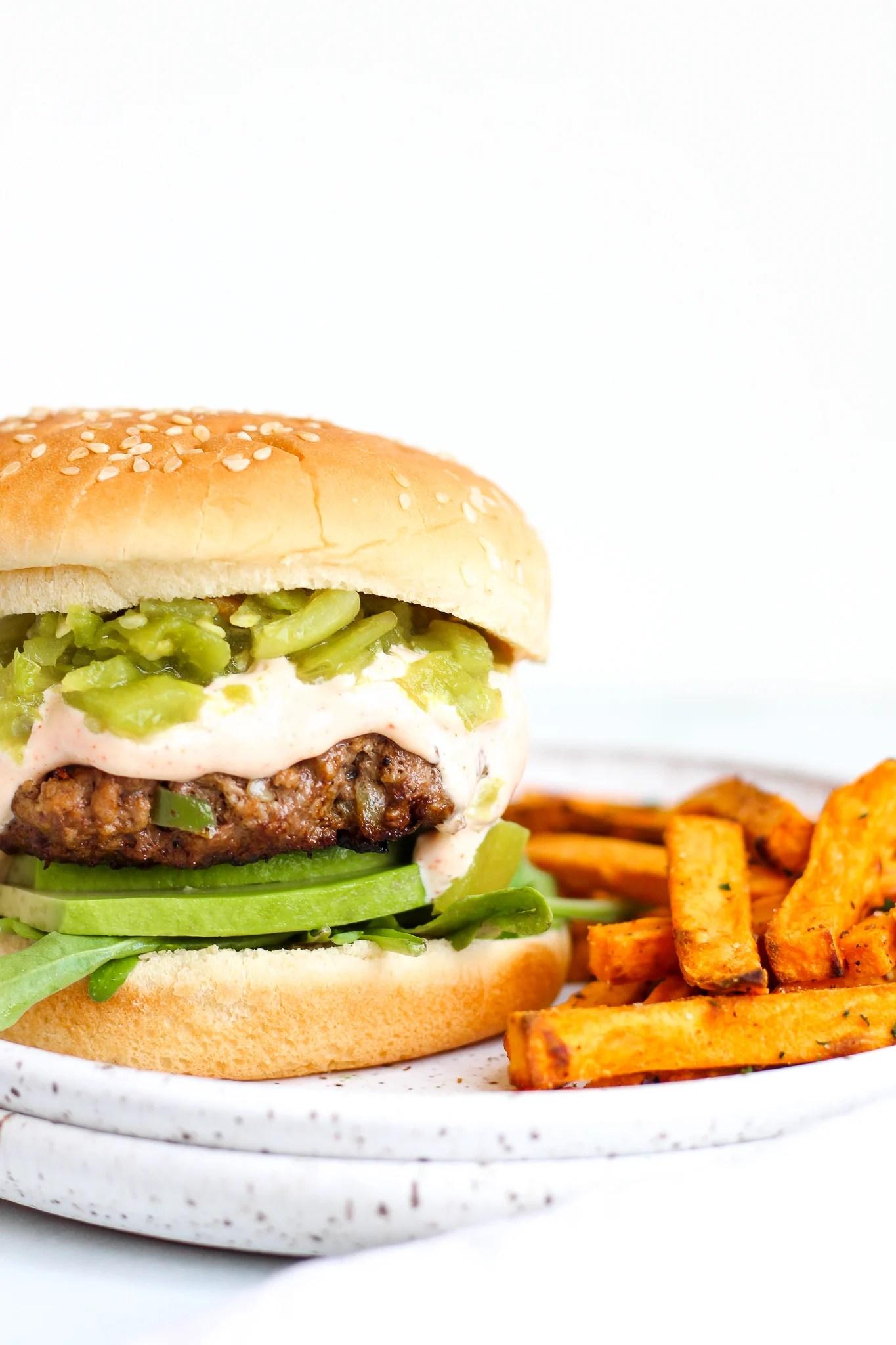 Green Chile burger on a sesame seed bun on a white ceramic plate served alongside homemade sweet potato fries