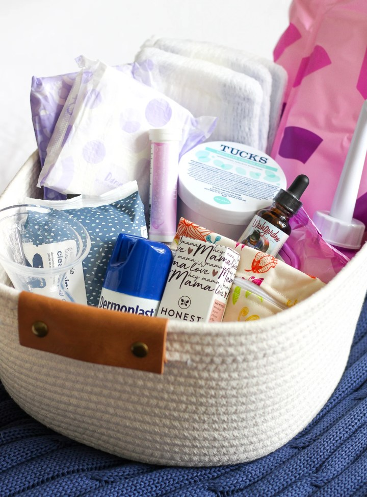 Basket on a bed filled with postpartum must haves for mama