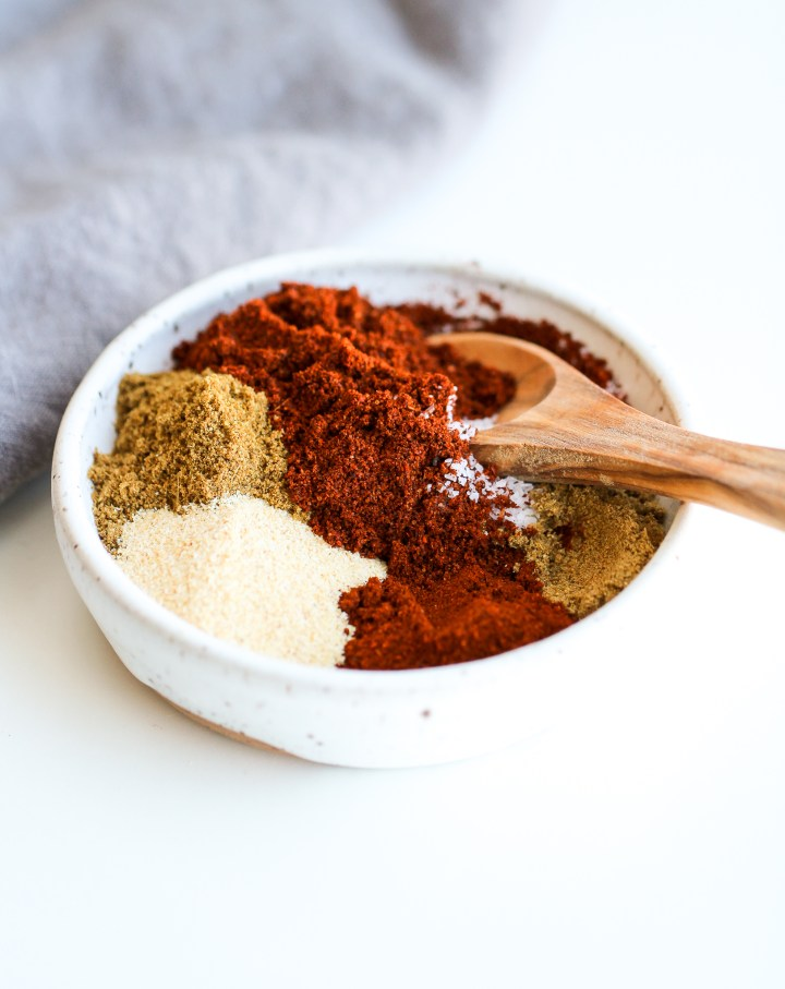 Spice mixture for instant pot fajita steak in a small white spice bowl with a small wooden spice spoon in it