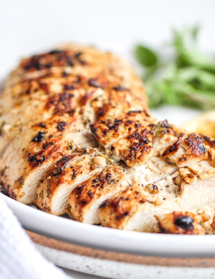 close up of sliced marinated greek chicken breast on a white plate with fresh oregano in the background
