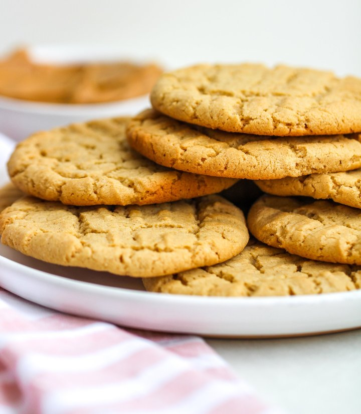 gluten free peanut butter cookies stacked on a white ceramic plate