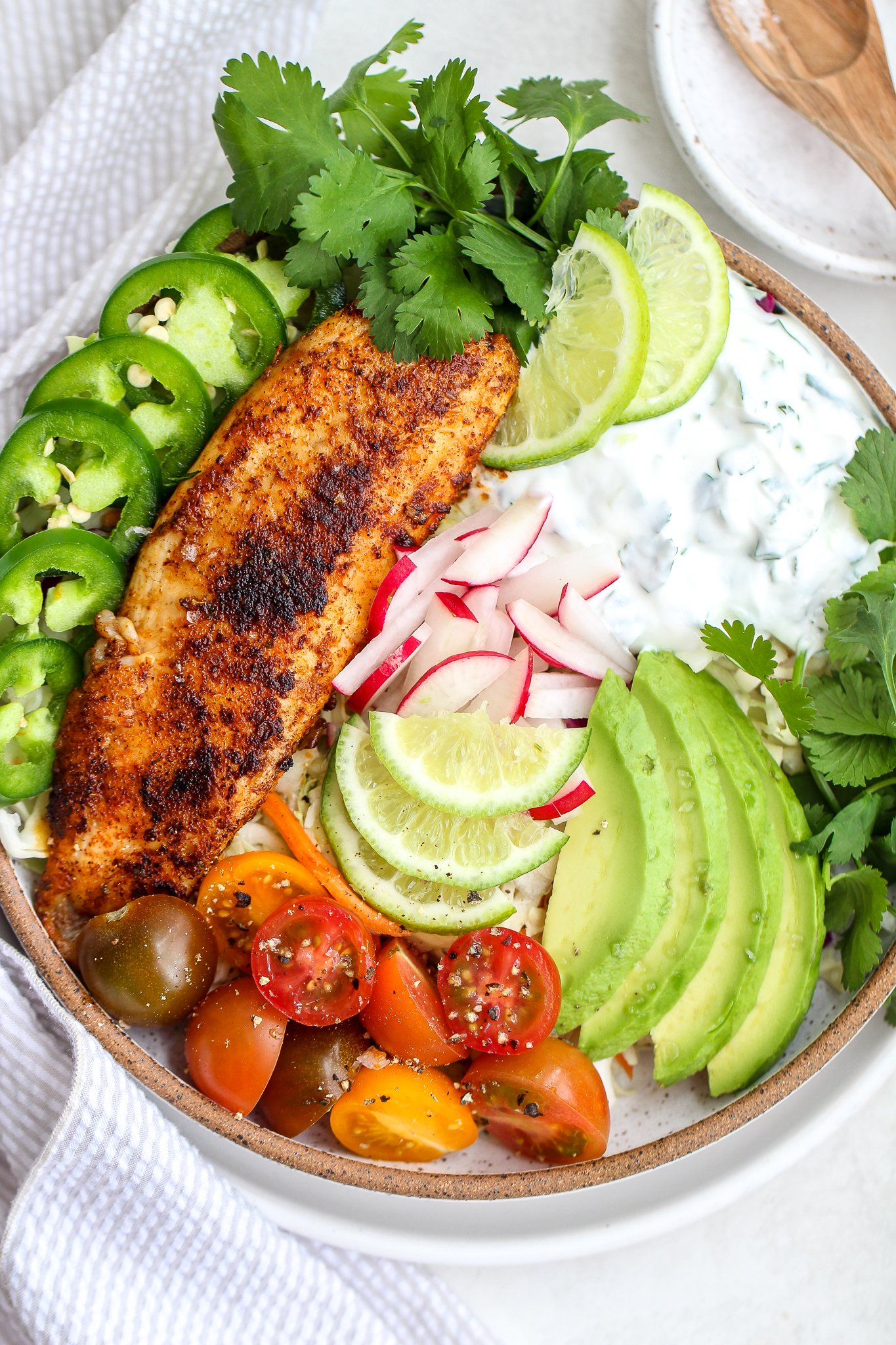 Fish taco bowls with blacked fish, cilantro lime cream sauce, fresh jalapeños, cilantro leaves, sliced lime, grape tomatoes and radishes