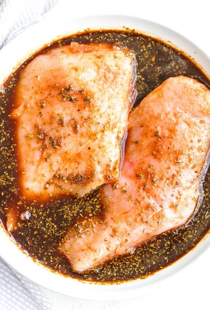 raw chicken breasts sitting in balsamic marinade