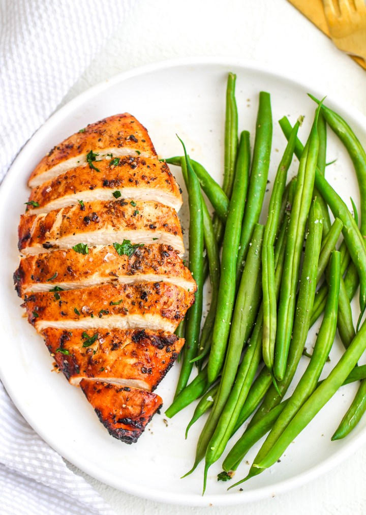 air fryer chicken breast sliced and served on a white ceramic plate topped with parsley and sea salt flakes and served with a side of fresh green beans
