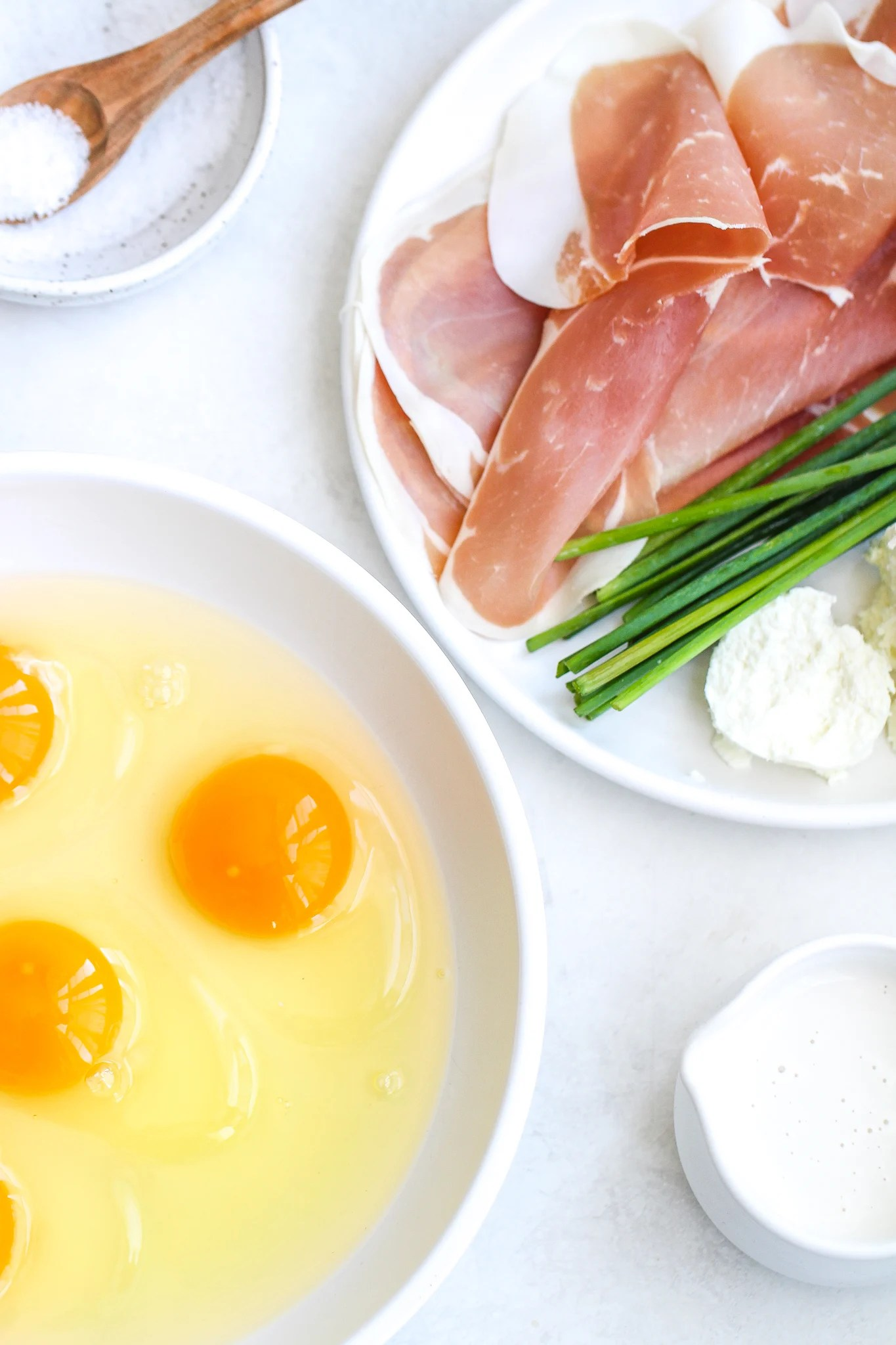 flat lay with raw eggs in a bowl, a ceramic cup with cream. Prosciutto, chives and goat cheese on a white ceramic plate and a sat dish with a wooden serving spoon