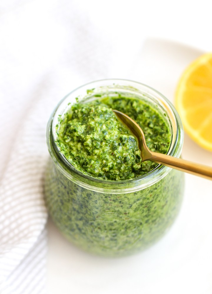 spinach, arugula & walnut pesto in a small glass jar with a matte golden spoon in it and a slice lemon on the side