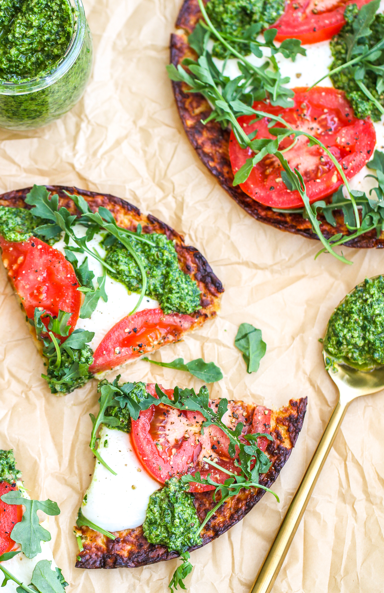low carb pesto pizza sliced and sitting on top of parchment paper. There is a gold spoon with pesto on it sitting next to the pizza and a jar of pizza in the upper right corner