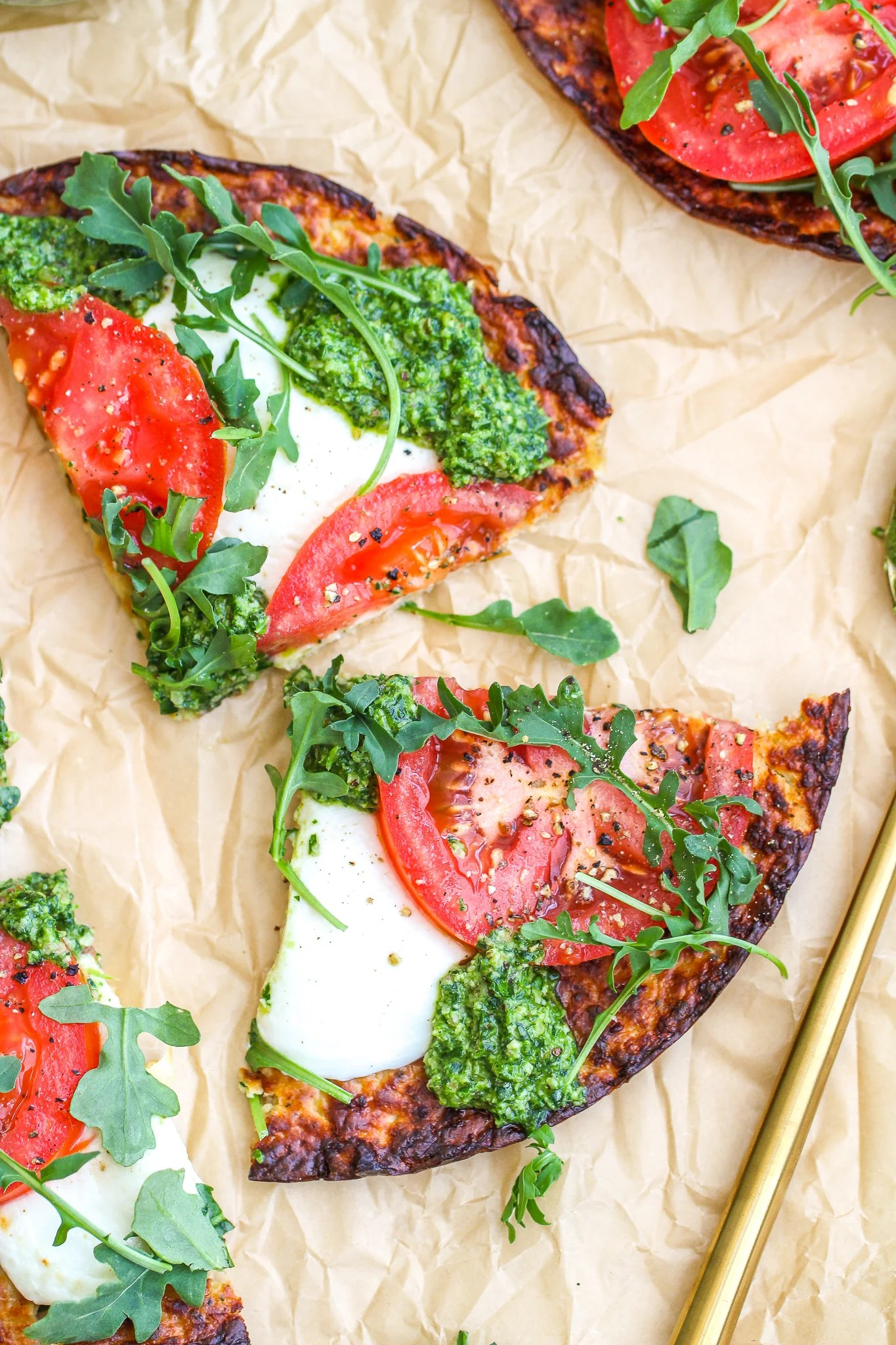 slices of low carb pesto pizza on a piece of parchment paper. The slices are topped with fresh sliced tomato and mozzarella along with fresh arugula and pesto