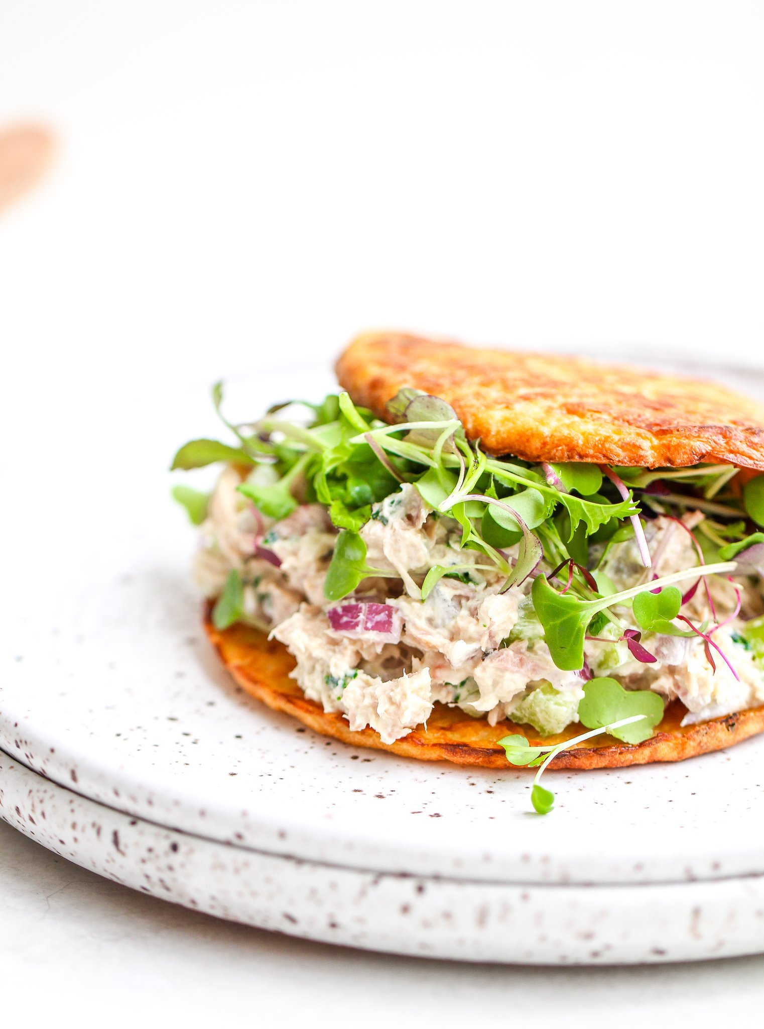 low carb tuna salad sandwiched between two toasted cauliflower thins and topped with fresh micro greens