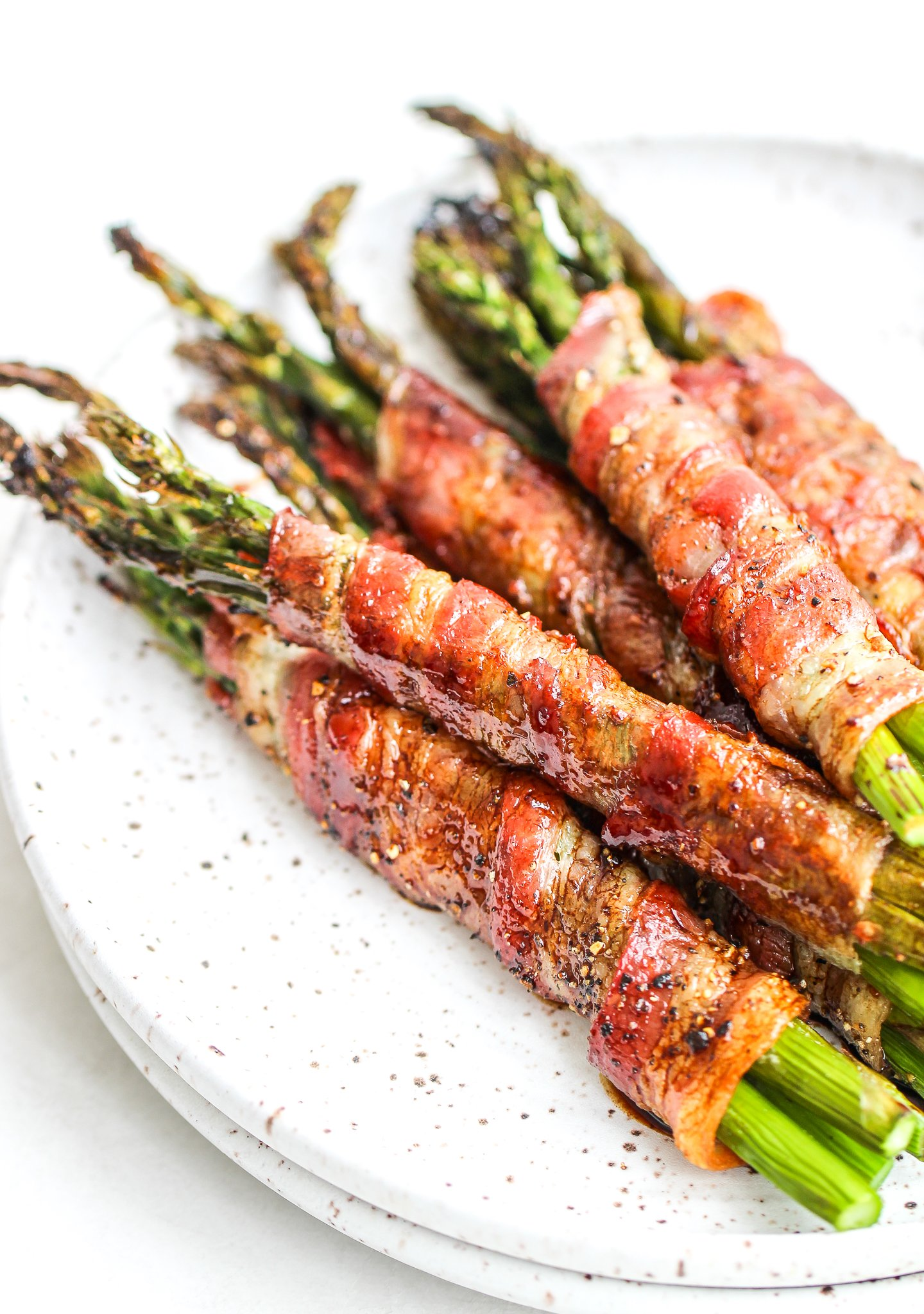 close up bacon wrapped asparagus bundles drizzled with balsamic reduction stacked on a ceramic plate with gold forks on the side of the plate
