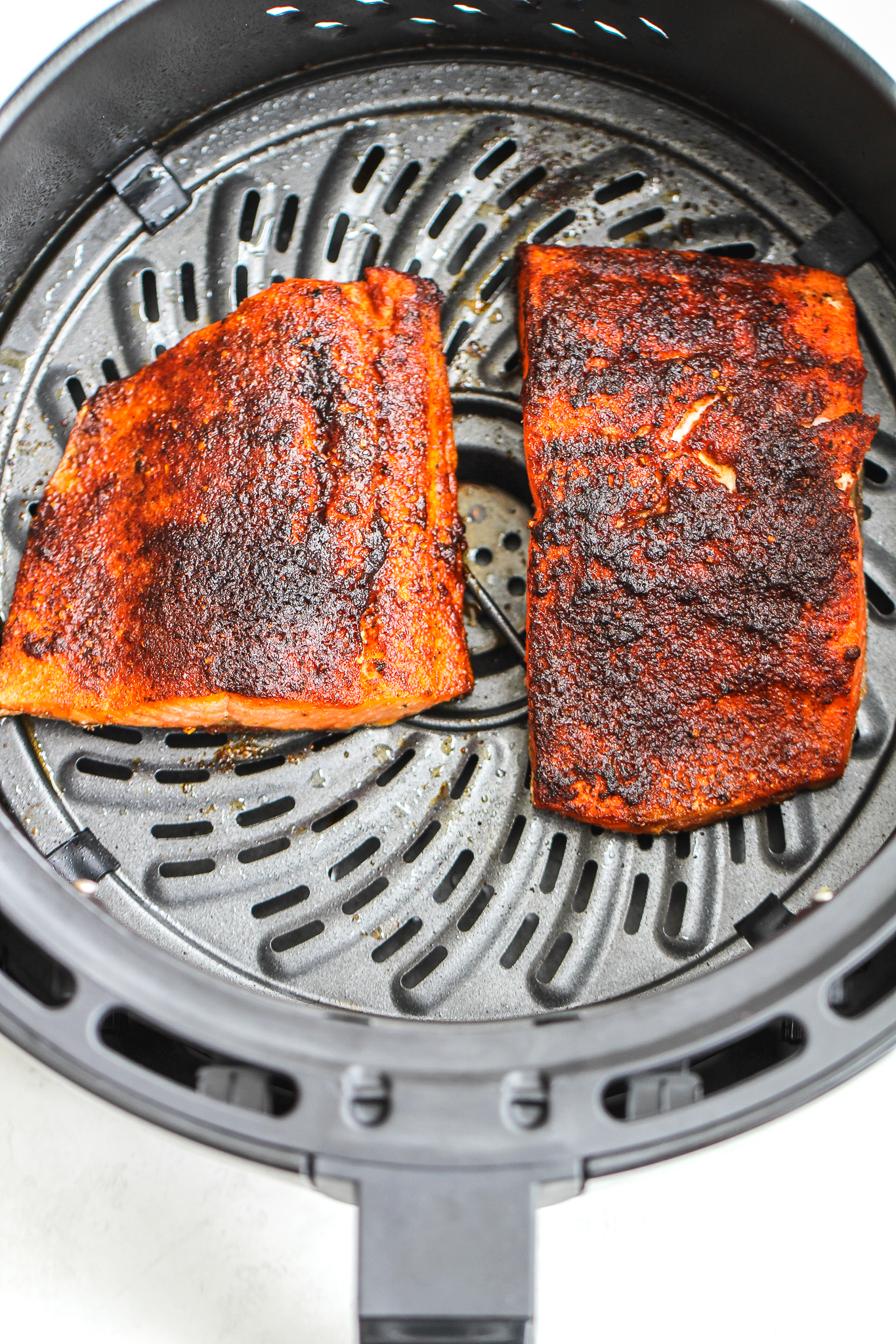 Cooked air fryer blackened salmon in an air fryer basket