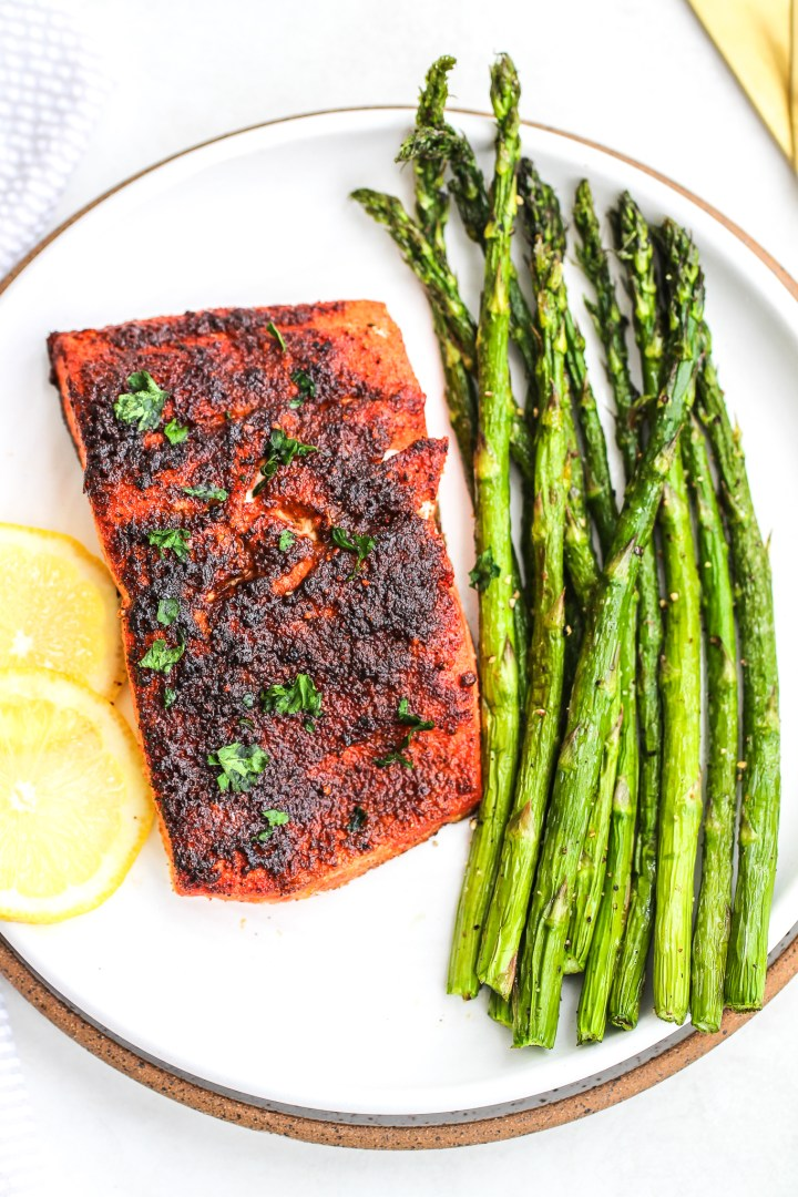 air fryer blackened salmon on a ceramic plate with sliced lemon and air fryer asparagus on the side