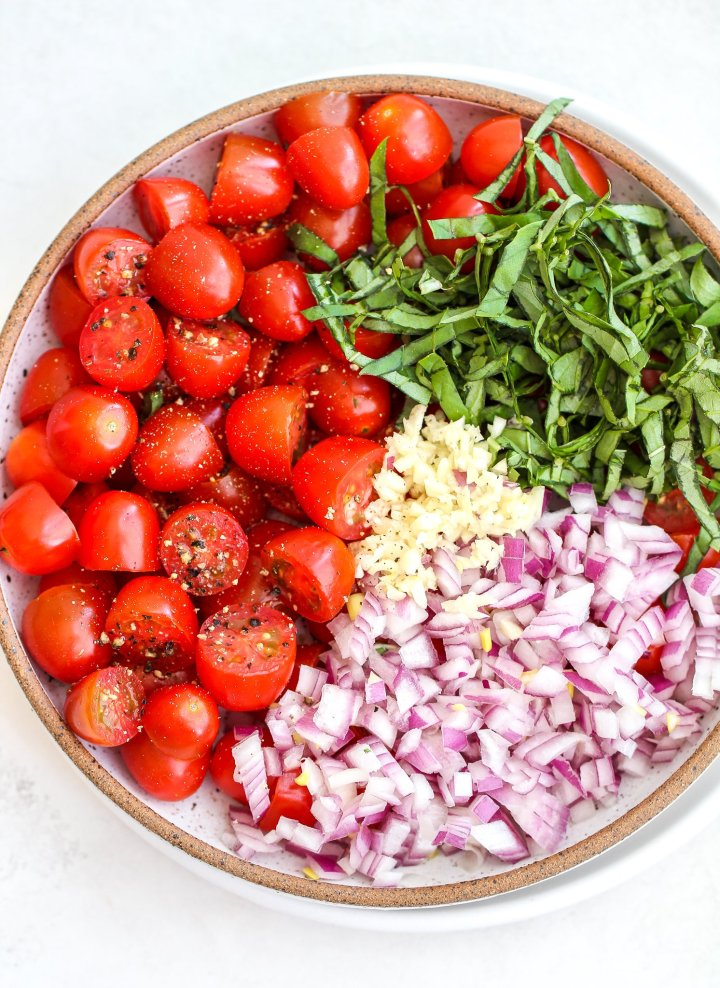 ceramic bowl filled with halved cherry tomatoes, fresh basil, diced red onion and minced garlic