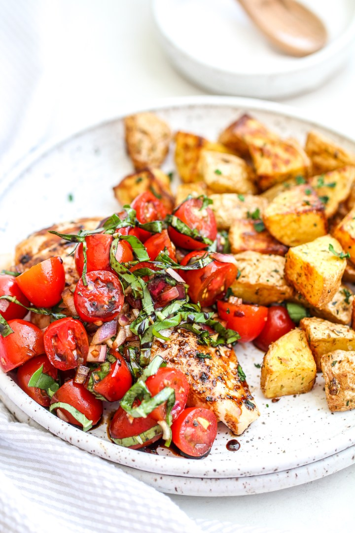 bruschetta chicken on a ceramic plate with a side of herb roasted potatoes