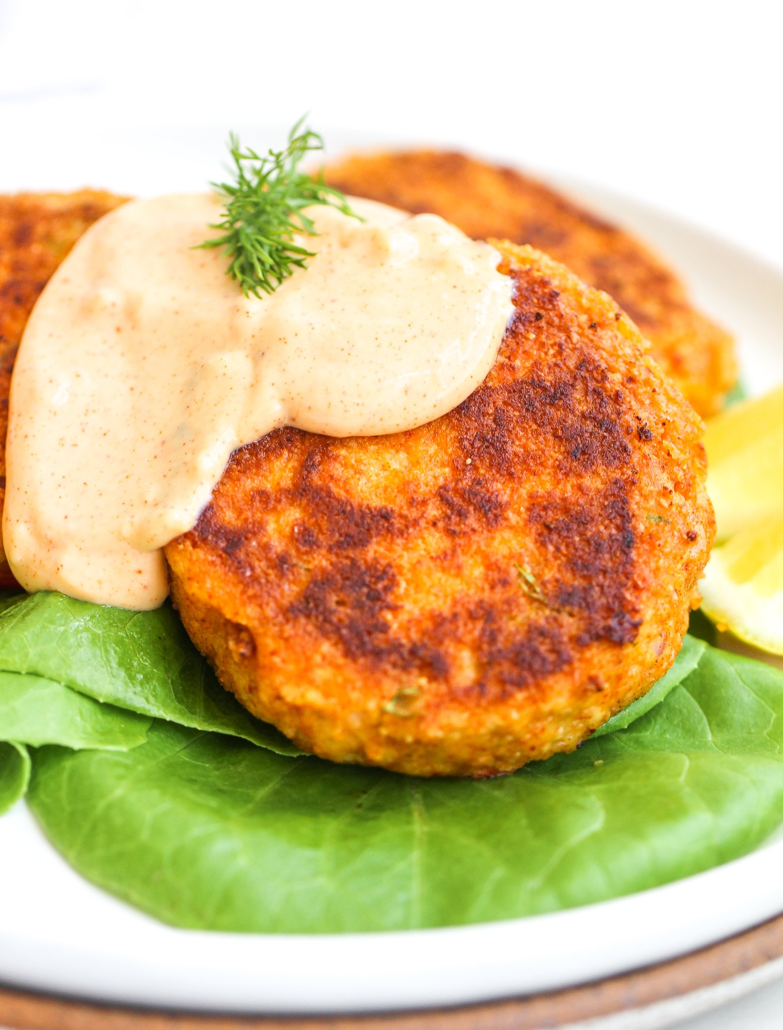 spicy garlic aioli drizzled over tuna cakes topped with fresh dill. The tuna cakes are stacked on top of a bed of butter lettuce with lemon wedges on the side