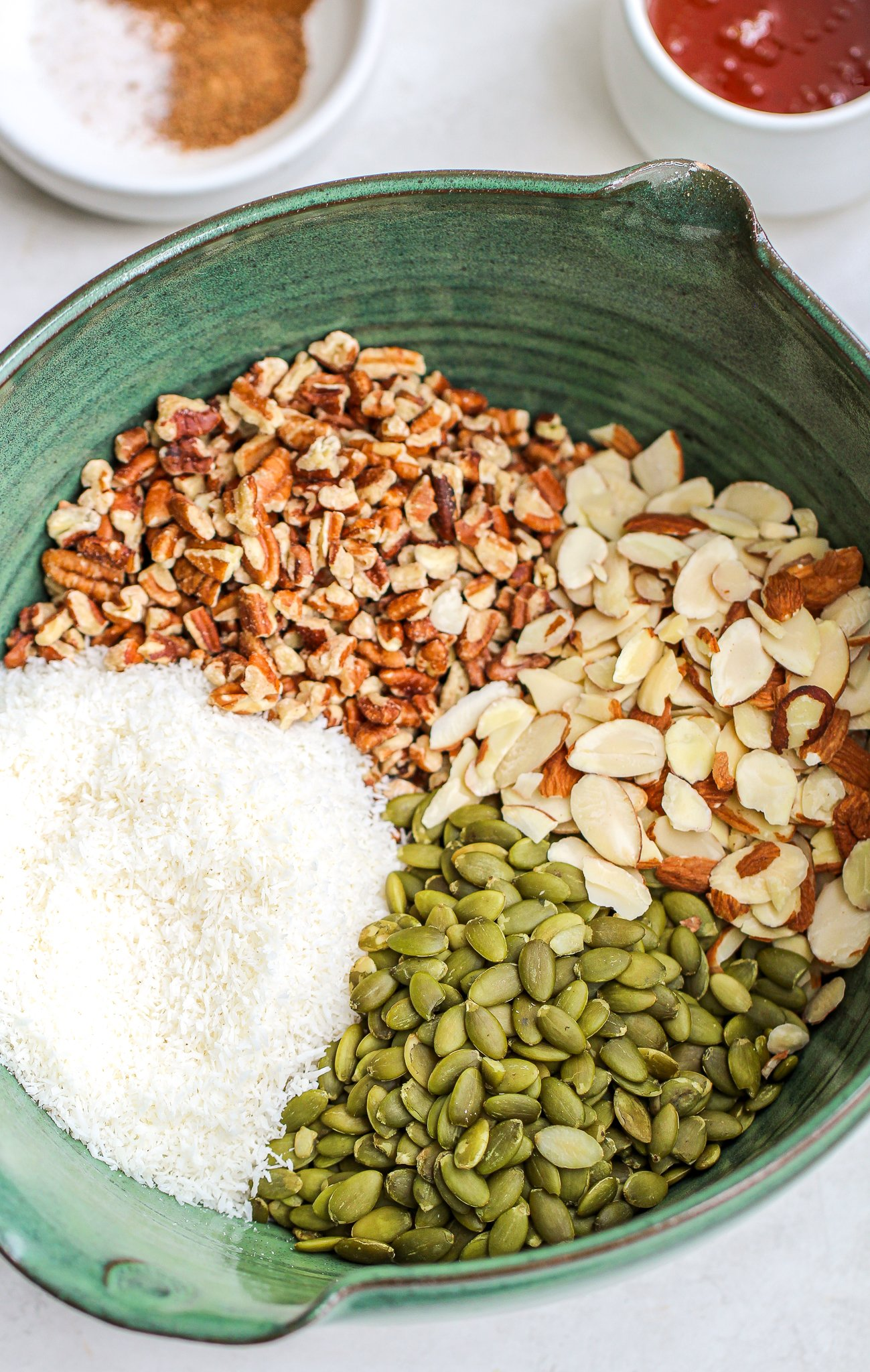 mix of sliced almonds, pecans, shredded coconut, and pumpkin seeds in a large green ceramic mixing bowl