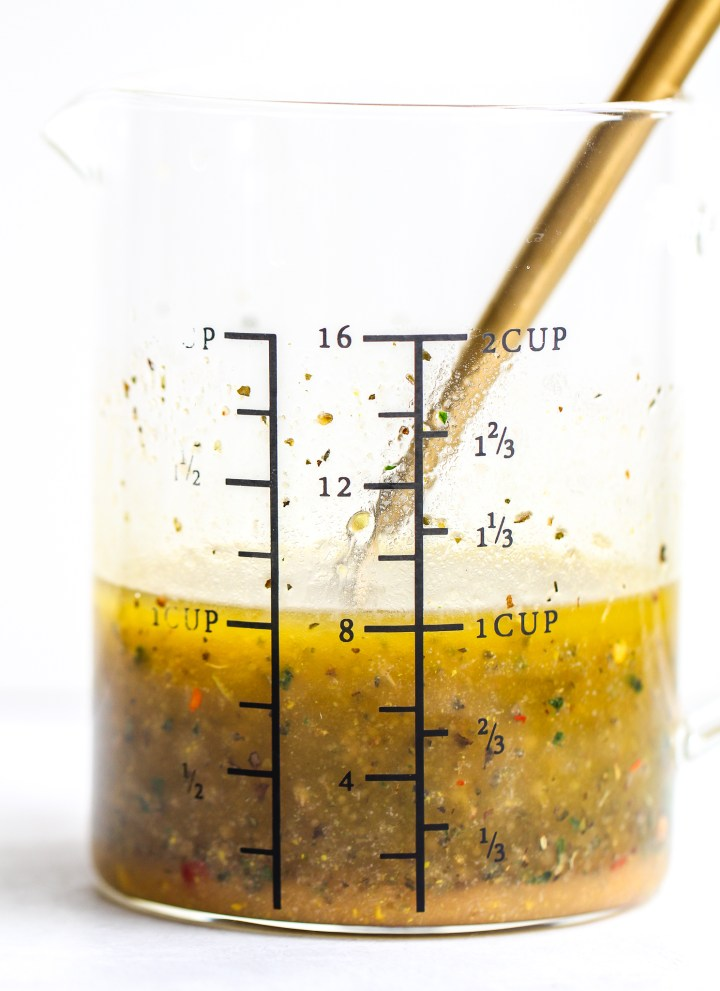 side view of homemade Italian dressing in a glass measuring jar. you can see the flecks of seasonings throughout the dressing. there is a gold fork sitting in the dressing