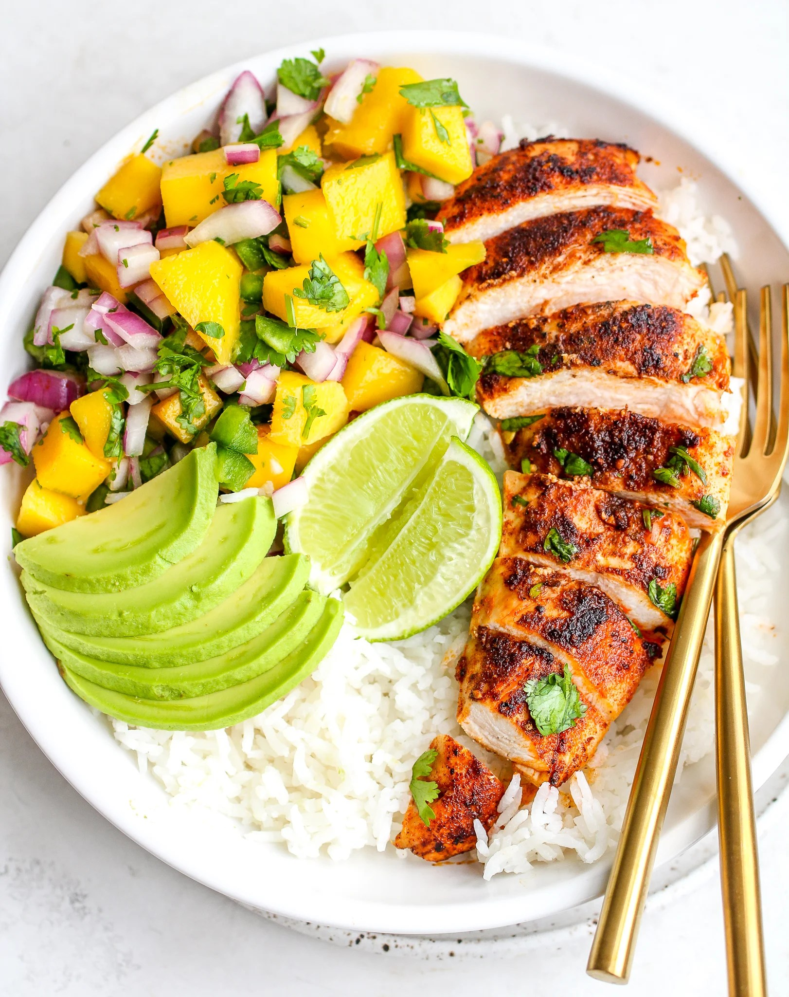 sliced spiced chicken breast over cooked white rice with fresh mango salsa on the side - as well as sliced avocado and lime wedges