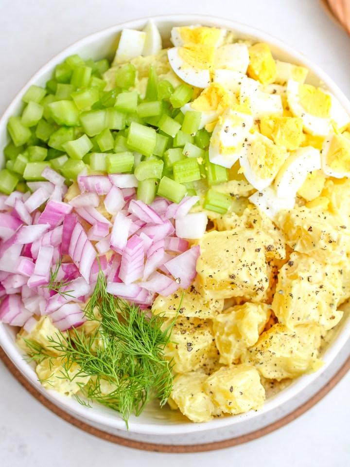 ingredients for classic potato salad in a serving bowl - cubed potatoes, diced celery and red onion, fresh dill and chopped hard boiled eggs