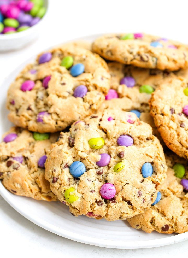 gluten free monster cookies piled on a white serving plate, the cookies are golden brown with colorful candies and chocolate chips throughout