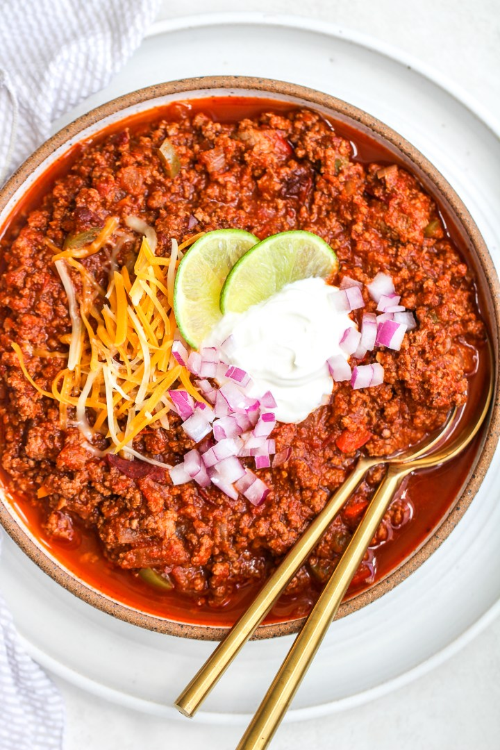 beef & bison chipotle chili in a speckled ceramic serving bowl with golden spoons in it. it is topped with sour cream, shredded cheese, lime slices and diced red onion
