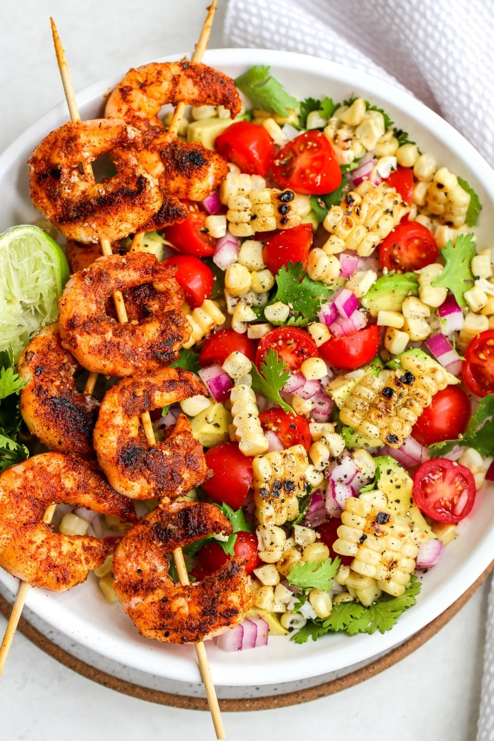 spiced grilled shrimp on wooden skewers laid over a white bowl layered with grilled corn, avocado, tomato, red onion and cilantro  There is a squeezed lime on the side of the bowl