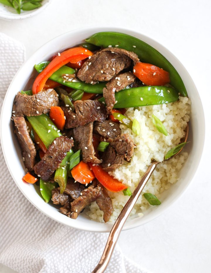 beef and veggies try fry in a white bowl - topped with white sesame seeds and fresh green onions
