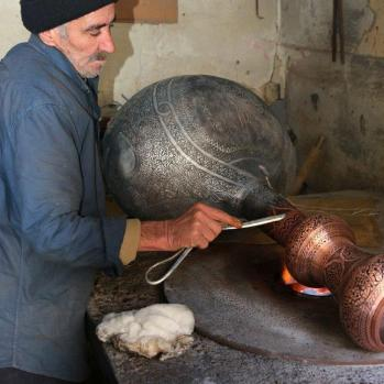 One of many skilled craftsmen working in the old town, Copper is engraved and hammered into shape, then fired and polished.