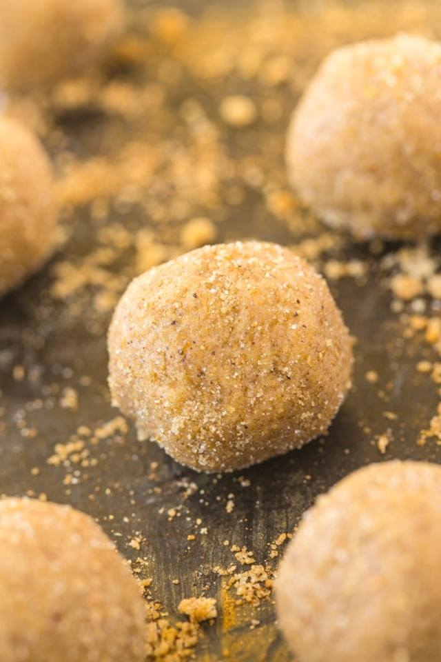 A gingerbread no bake energy ball covered in gingerbread spices and with cinnamon around it