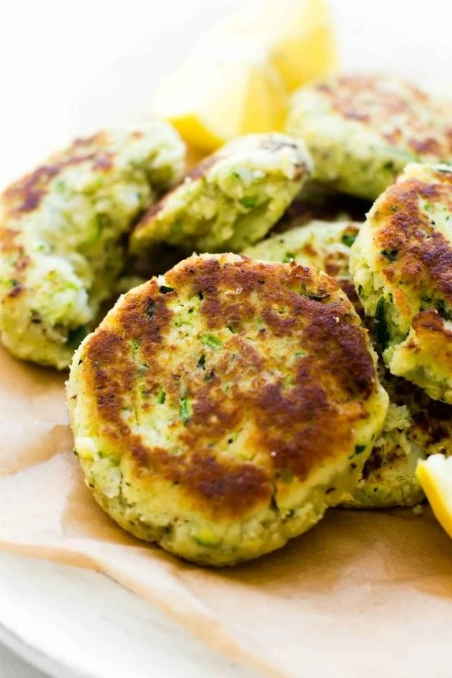 A plate of zucchini cauliflower fritters laying on a plate