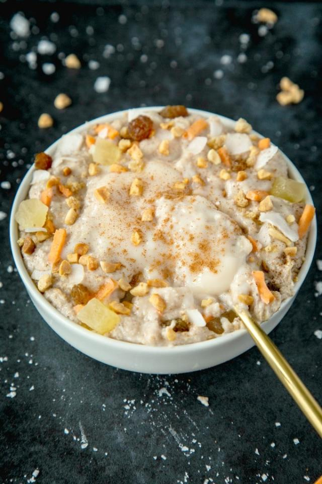 A white bowl filled with keto carrot cake oatmeal and topped with shredded carrots, walnuts, raisins, dried pineapple and a pool of coconut butter frosting.