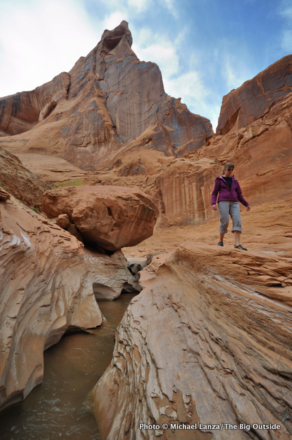 A hiker upstream from Coyote Natural Bridge in Coyote Gulch.