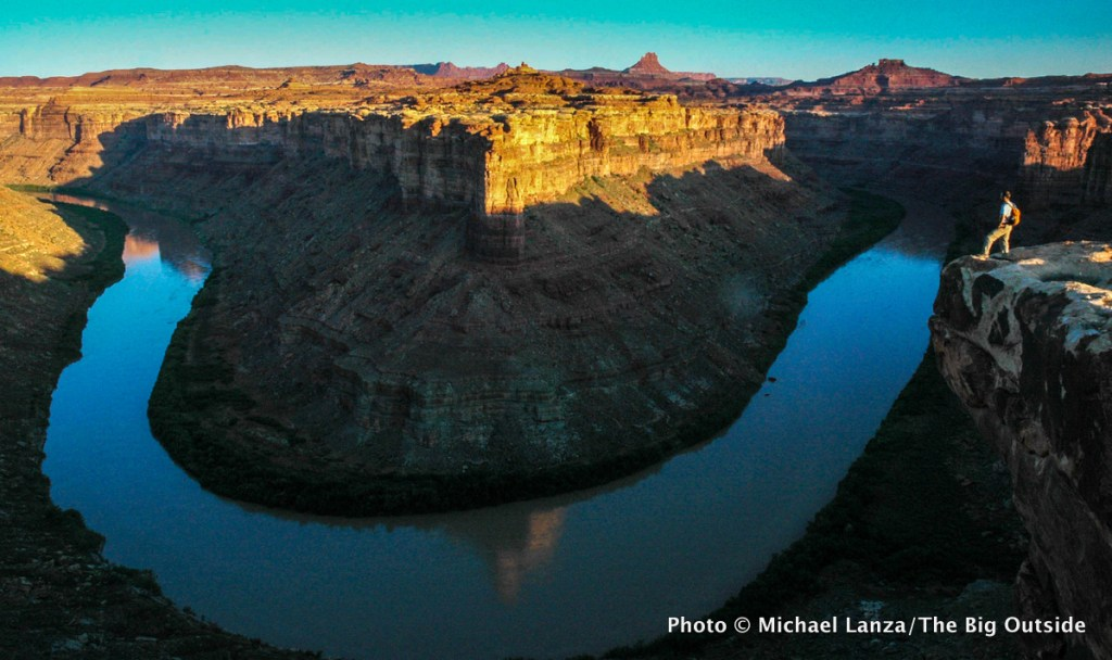 A hiker in early morning above Stillwater Canyon on the Green River in Canyonlands National Park.