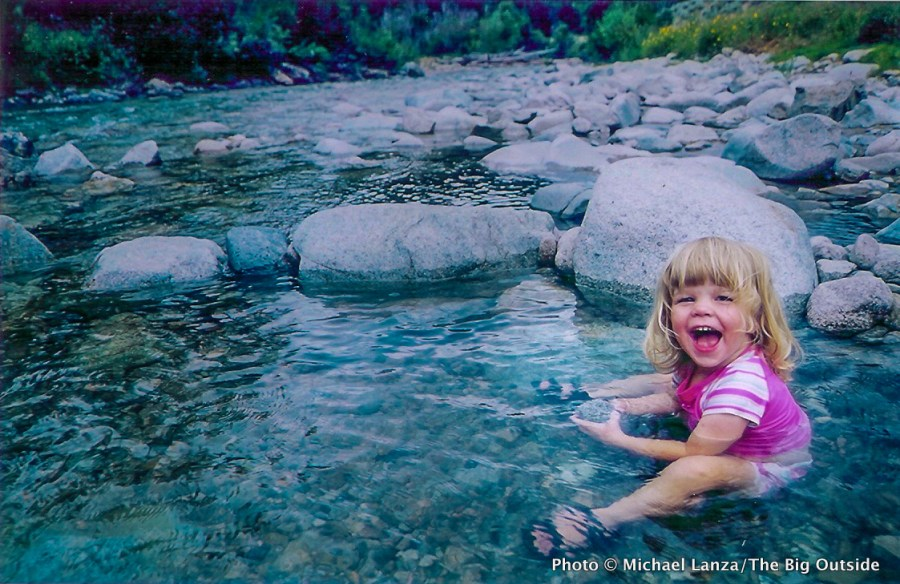 A toddler girl sitting in Skillern Hot Springs in Idaho's Smoky Mountains.