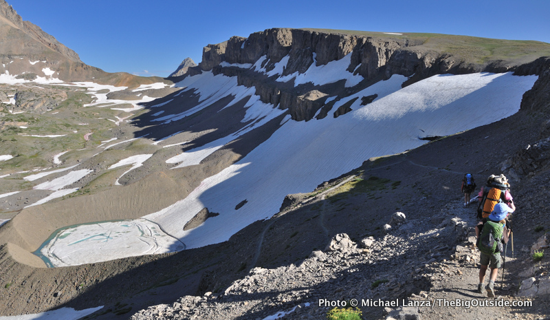 Backpackers on the Teton Crest Trail above the Schoolroom Glacier and South Fork Cascade Canyon.