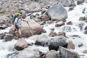 A backpacker crossing Eliot Creek on the Timberline Trail around Oregon's Mount Hood.