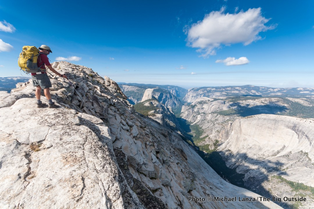 A backpacker hiking over Yosemite's Clouds Rest, with Yosemite Valley in the distance.