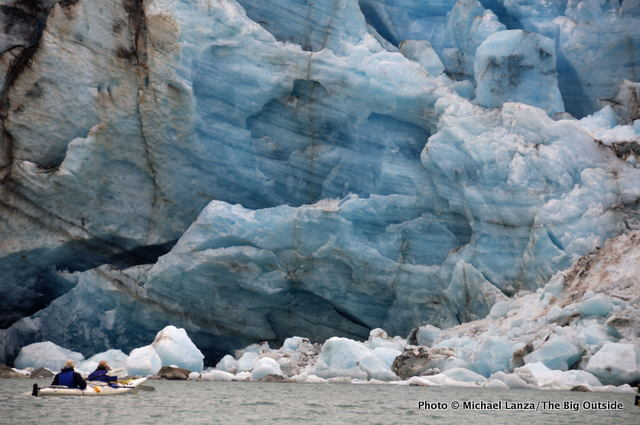 Kayakers passing the Lamplugh Glacier in Glacier Bay National Park.