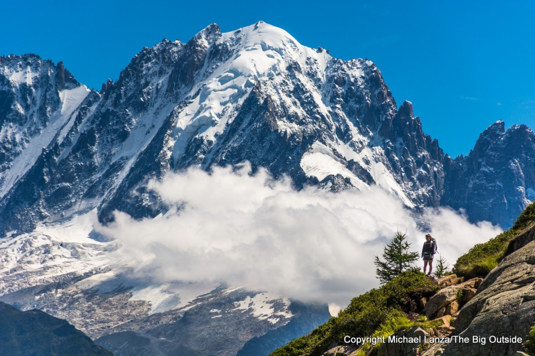 A hiker on a trail overlooking the Mont Blanc massif in Switzerland.