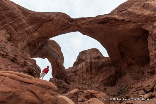 Teenage boy below Double Arch, Arches National Park.