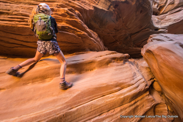 Young girl scrambling on a hike in Crack Canyon, in Utah's San Rafael Swell.