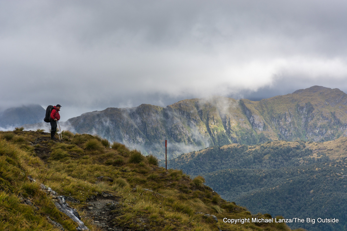 A backpacker hiking in rain on the Dusky Track in Fiordland National Park, New Zealand.