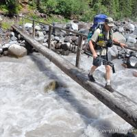 A backpacker crossing Winthrop Creek on the Wonderland Trail in Mount Rainier National Park.