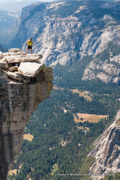 """A hiker standing on """"The Visor"""" atop Half Dome in Yosemite National Park."""