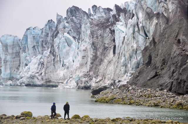 Kayakers hiking below the Lamplugh Glacier, Glacier Bay, Alaska.