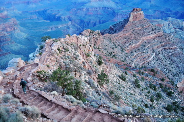 A hiker descending the Grand Canyon's South Kaibab Trail before dawn.