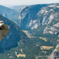 A hiker atop Half Dome, high above Yosemite Valley in Yosemite National Park.