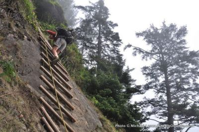 A backpacker descending a rope ladder on the coast of Olympic National Park.