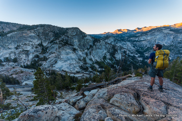A backpacker at dawn above the Lyell Fork Canyon of the Merced River in Yosemite National Park.