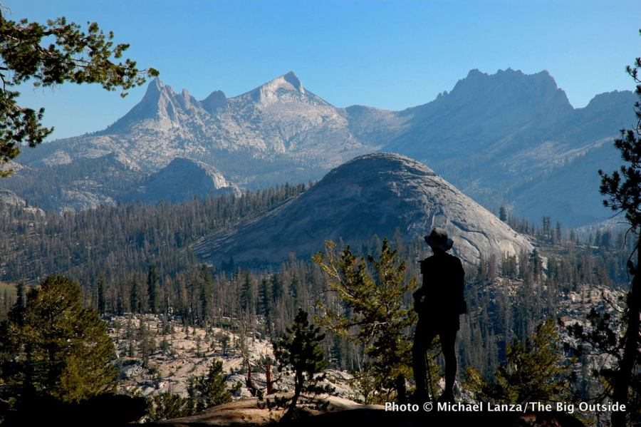 A backpacker on the John Muir Trail overlooking the Cathedral Range in Yosemite National Park.